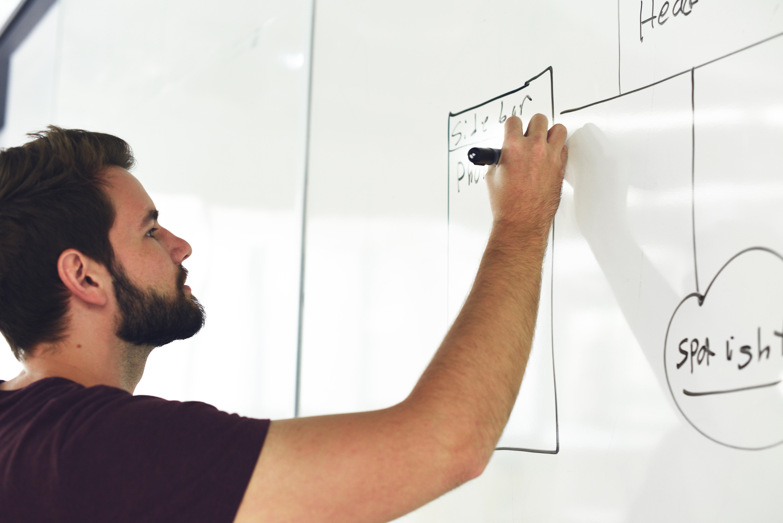 jeune commercial qui dessine sur un tableau blanc